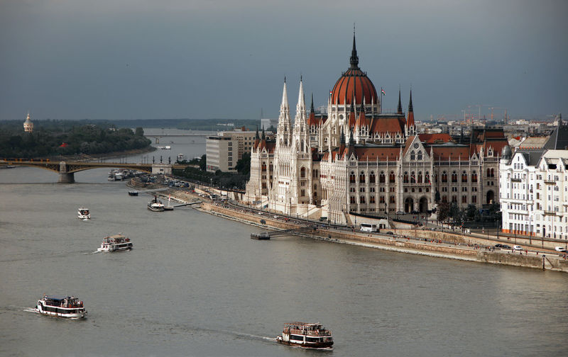 Boats in river by hungarian parliament building in city