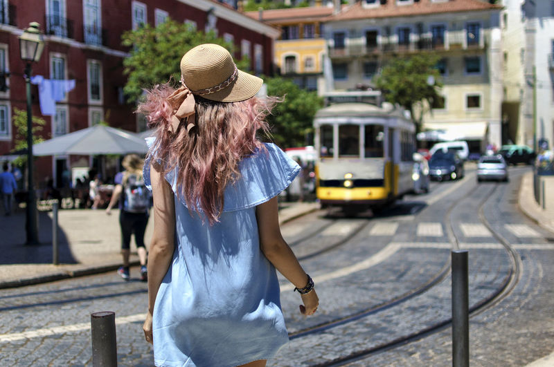 Rear View Of Young Woman Walking On Street In City