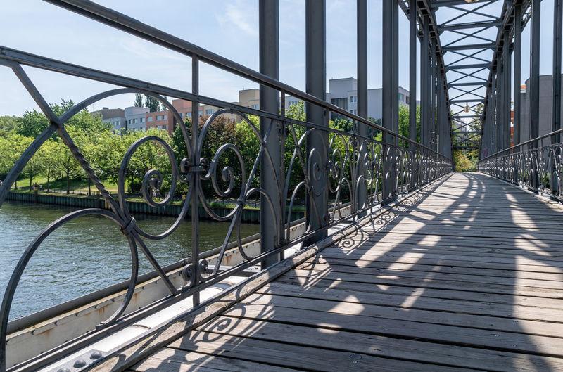 Footbridge over river in city against sky