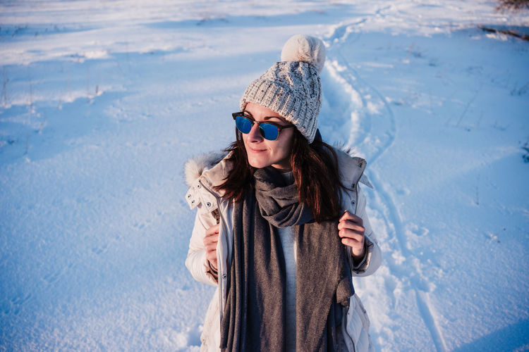 Young woman standing on snow covered landscape
