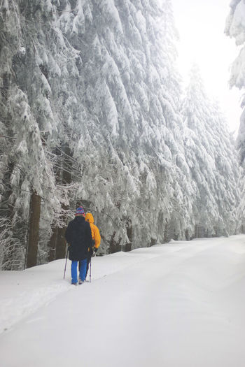 Rear view of people walking on snow covered mountain