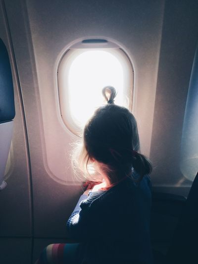Side view of girl looking through window in airplane