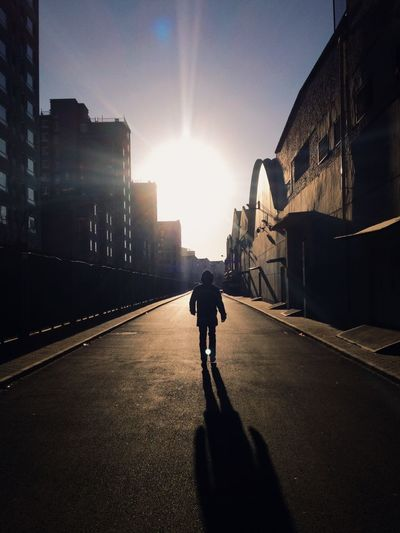 Rear view of young man walking on road amidst buildings on sunny day