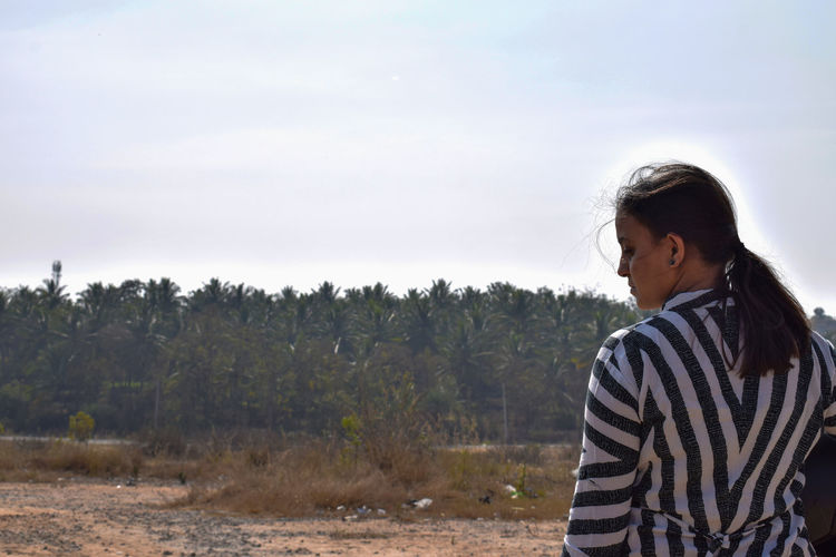 Rear view of young woman wearing striped top while standing on land against sky