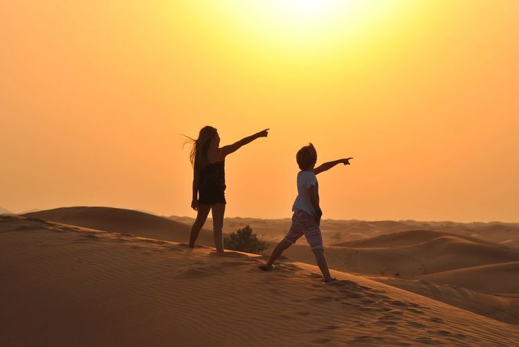 It's over there! Sunset Child Sky Childhood Family Land Offspring Fun Positive Emotion Beauty In Nature Leisure Activity Sand