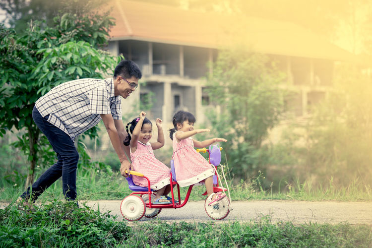 Full Length Of Sisters Riding Tricycle With Father On Road At Public Park