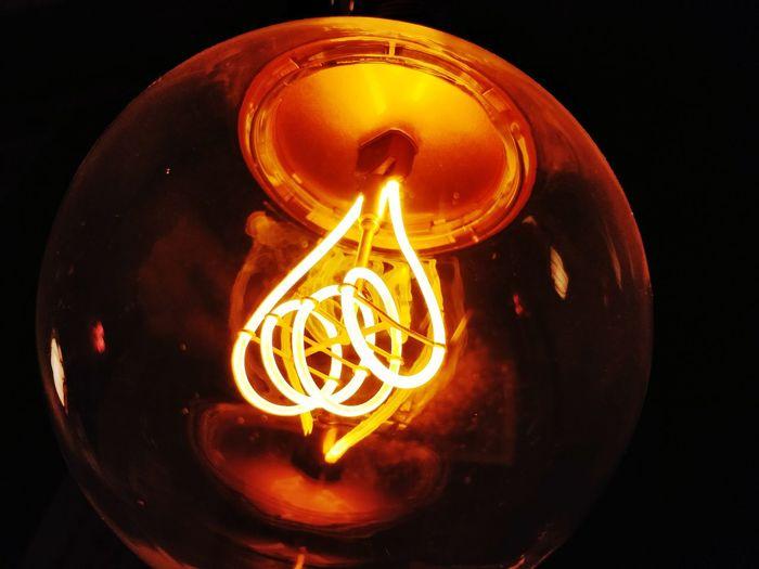 Black Background Filament Illuminated Light Bulb Close-up
