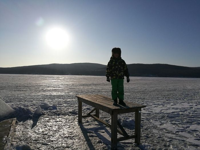 Boy standing on table at snow covered field against clear blue sky