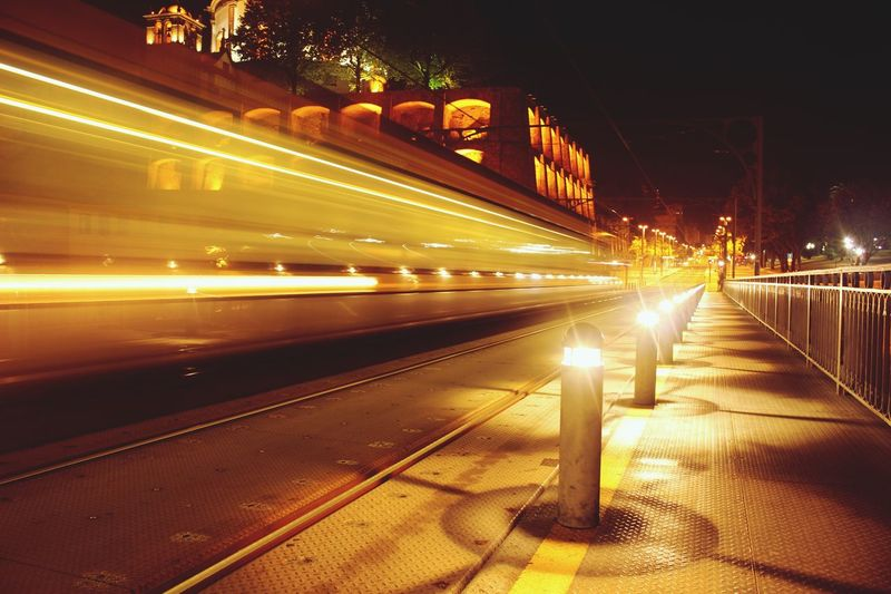 Blurred Motion Of Illuminated Cable Car On Street In City At Night