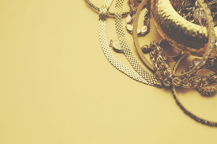 High Angle View Of Gold Jewelry Over Yellow Background