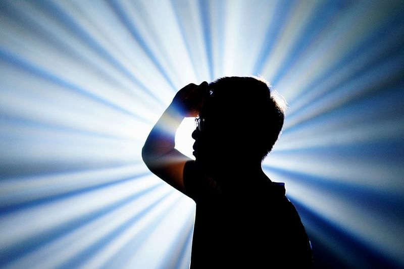 Young man gesturing against light beams