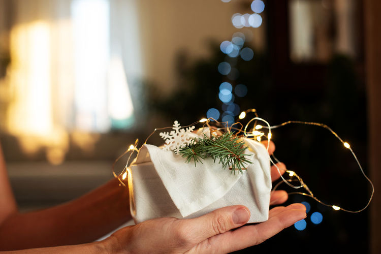 Christmas gift in hands. packaging in eco-friendly materials, furoshiki fabric. bokeh