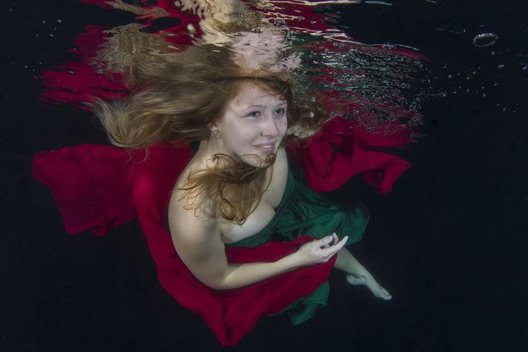 Beautiful Young Woman Swimming In Pool At Night