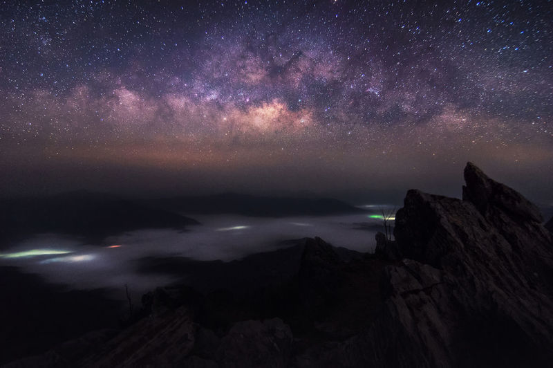 Scenic view of rocky mountains against star field sky at night