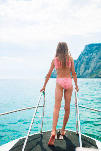 Rear view of girl in bikini on boat in sea