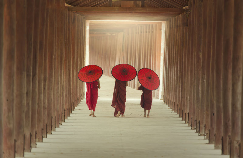 Rear view of monks with paper umbrella walking on walkway of pagoda
