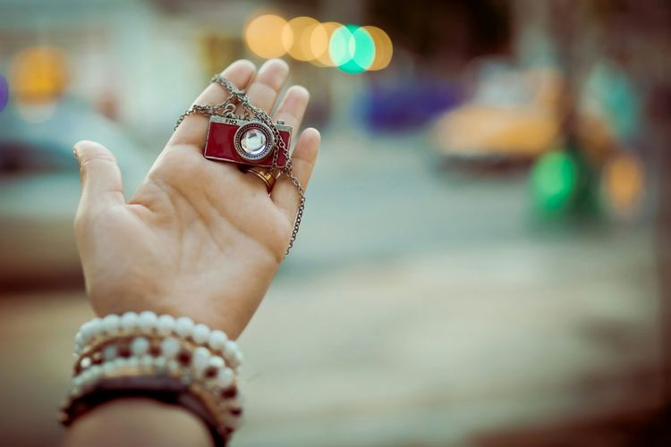 Cropped image of woman holding camera key ring