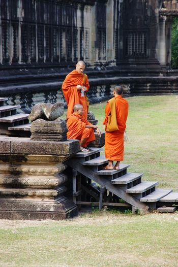 Buddhist monks EyeEmNewHere Journey Spiritual Sitting Standing Stairs Steps Young Angkor Wat Buddhist Buddhism Temple Orange Robes Robes Ancient Temple Buddhist Monks Monks Religion Architecture Built Structure Spirituality Belief Orange Color Place Of Worship Day History Building People The Past Men EyeEmNewHere