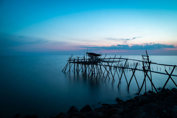 Wooden jetty at the rocky seaside during blue hour. Long Exposure Water Sky Sea Tranquil Scene Scenics - Nature Beauty In Nature Tranquility Cloud - Sky Architecture Nature Horizon Over Water Non-urban Scene Horizon Built Structure Idyllic Sunset No People Pier Dusk Outdoors Fishing Industry Long Exposure