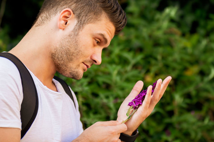 Side view of young man holding purple outdoors