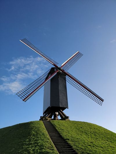 Low angle view of traditional windmill on field against clear sky