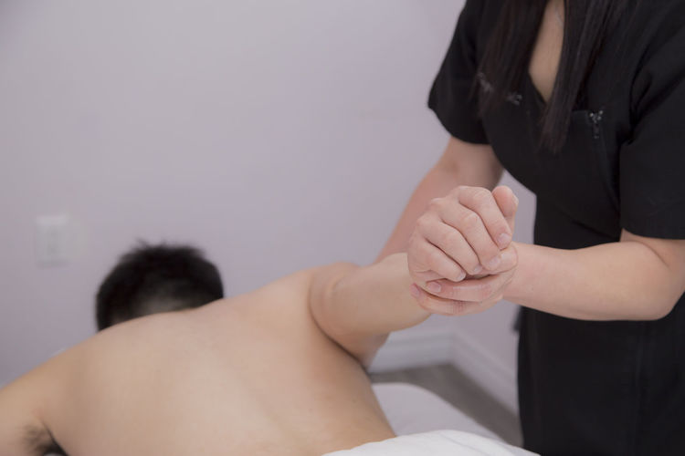 Midsection Of Woman Giving Hand Massage On Man At Spa