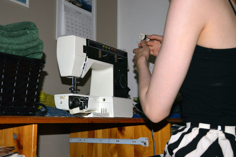 Midsection of woman sitting by sewing machine on table