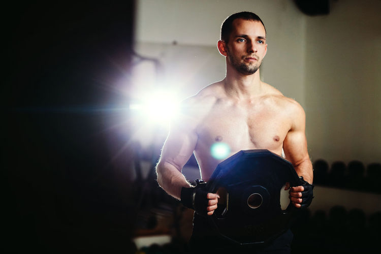 Shirtless Male Athlete Training In Gym
