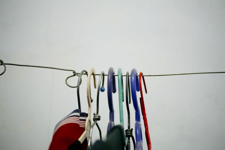 Hanging Clothing Coathanger Multi Colored No People Close-up Clothesline In A Row Clothes Rack Indoors  Copy Space Clothespin Cable Group Of Objects Still Life Side By Side Wall - Building Feature Order