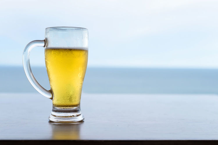 Glass of beer on table against sea