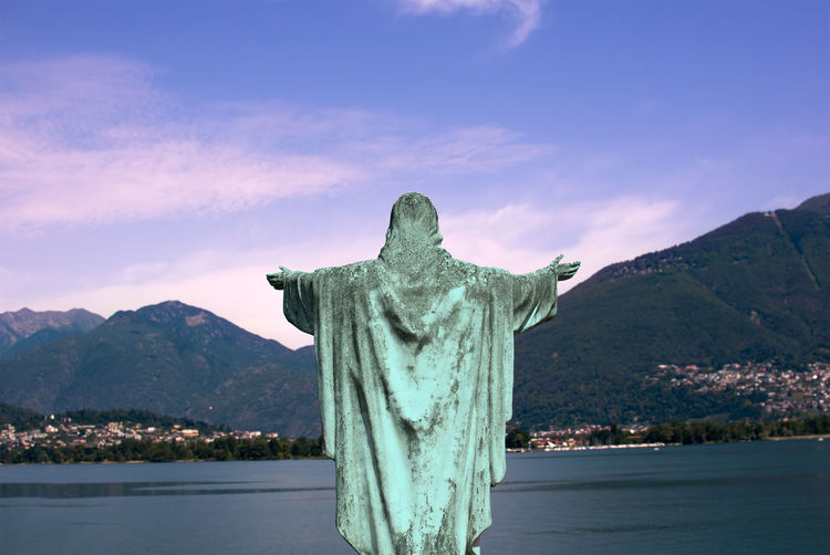 Statue by mountain against sky