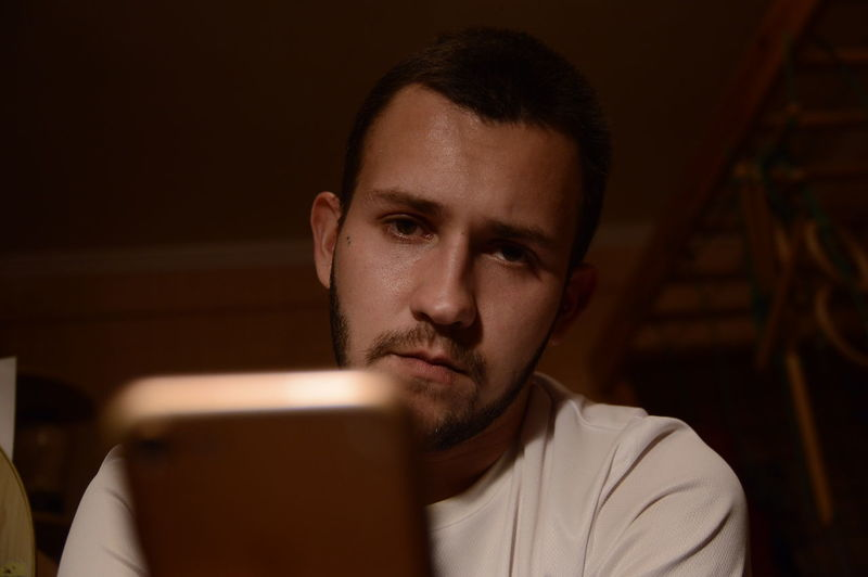 Close-up of young man using smart phone at home