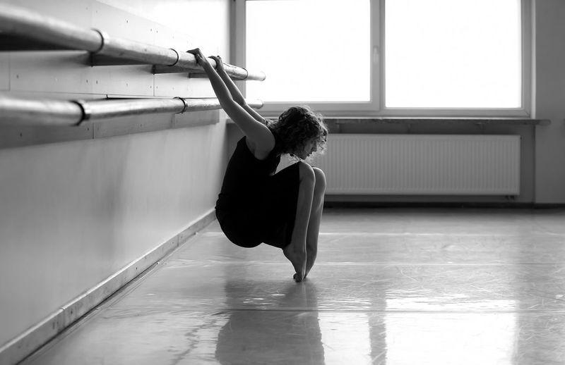Teenage girl stretching at ballet studio