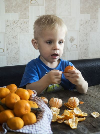 Boy Having Oranges While Sitting On Sofa At Home