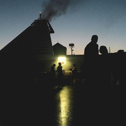 Silhouette people at illuminated temple against sky at night