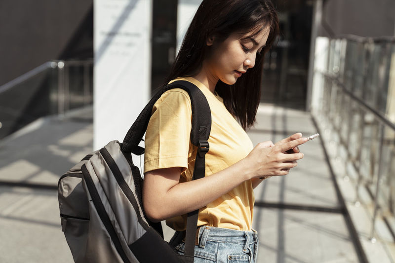 Young woman using mobile phone while standing indoors