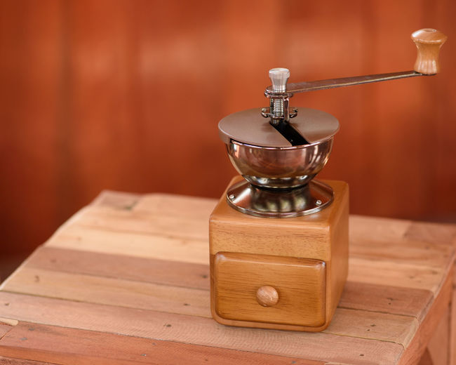 Close-up of vintage coffee grinder on wooden table