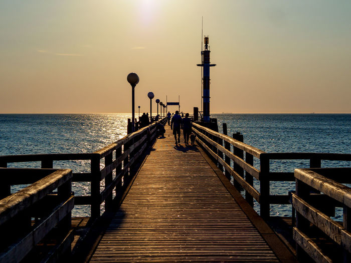 People on pier over sea against sky during sunset