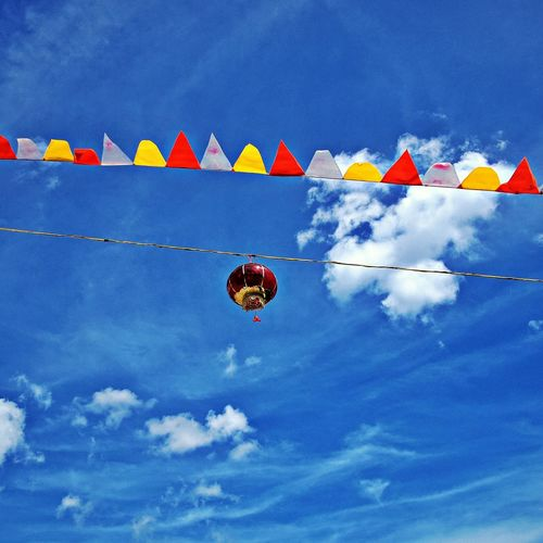 Low Angle View Of Pot And Paper Decoration Hanging On Rope Against Blue Sky
