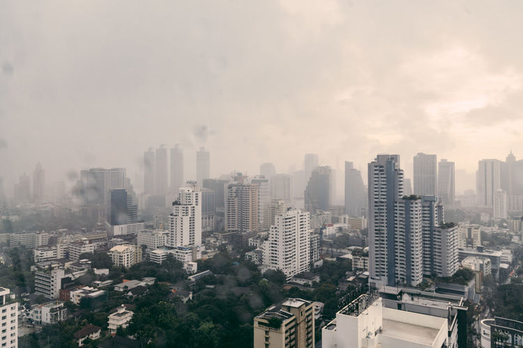 Rain over Bangkok: Cityscape and cloud while raining in the evening. Architecture Building Building Exterior Built Structure City Cityscape Cloud - Sky Day Financial District  Fog High Angle View Landscape Modern Nature No People Office Building Exterior Outdoors Pollution Residential District Sky Skyscraper Smog Tall - High Urban Skyline