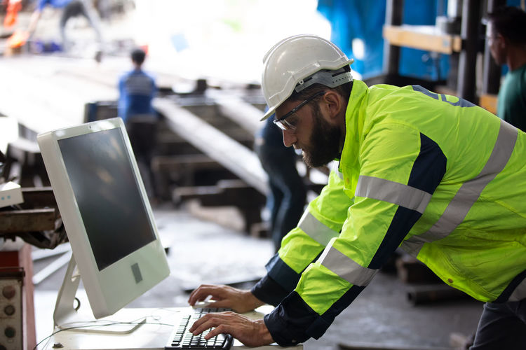 Side view of engineer using computer in factory