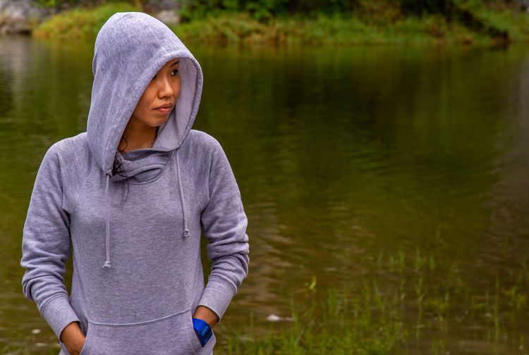 Beautiful woman with hands in pocket standing by lake
