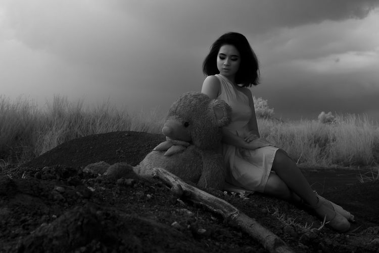 Young woman with teddy bear sitting on field against sky