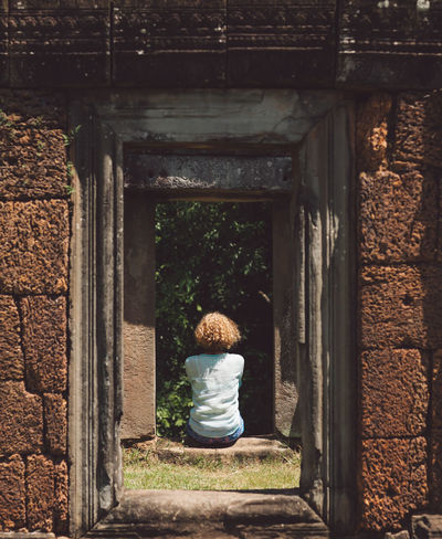 Siem Reap Cambodia Angkor Curly Hair Girl Rear View One Person Real People Childhood Day Full Length Architecture Lifestyles Child Casual Clothing Women Leisure Activity Sitting Built Structure Nature Men Outdoors Females Standing Architectural Column