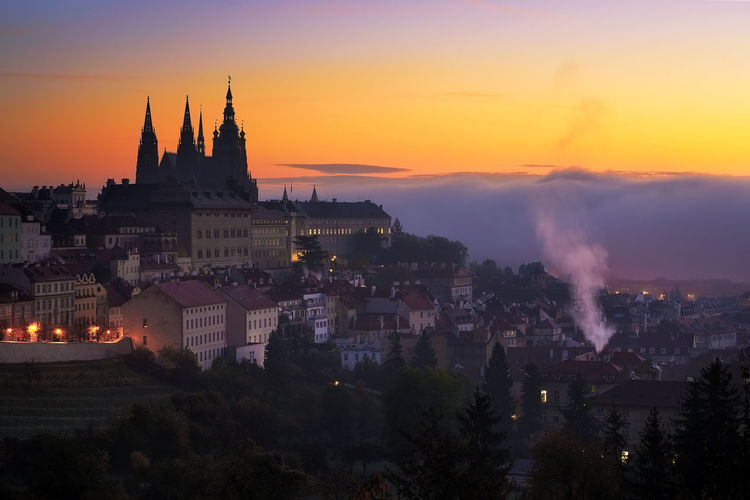 Morning view at Saint Vitus cathedral in Prague. Amazing sunrise foggy detail of gothic castle. Typical spring season city in Czech republic. Built Structure Architecture Outdoors Prague Czech Republic Unesco History Charles Bridge Building Exterior Sunset City Building Sky Orange Color Nature No People Residential District Cityscape Tree Travel Destinations Illuminated Smoke - Physical Structure Dusk Plant Religion Pollution