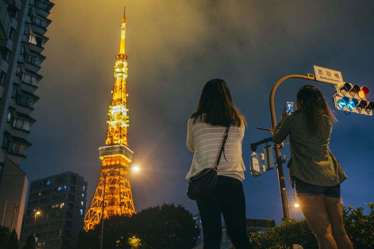 Rear view of woman photographing illuminated tokyo tower against sky at night