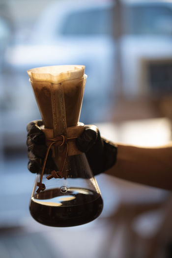 Black Coffee inside Lab Glass in Hand Ijas Muhammed Photography Focus On Foreground Close-up No People Food And Drink Coffee - Drink Still Life Coffee Metal Day Wood - Material Table Hanging Indoors  Drink Refreshment Old Brown Selective Focus Bell