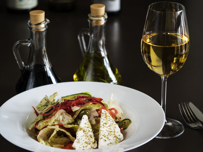 High angle view of greek salad with white wine on table