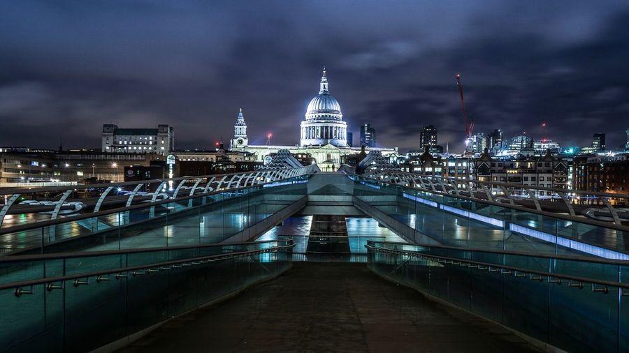 View of illuminated bridge and buildings at night