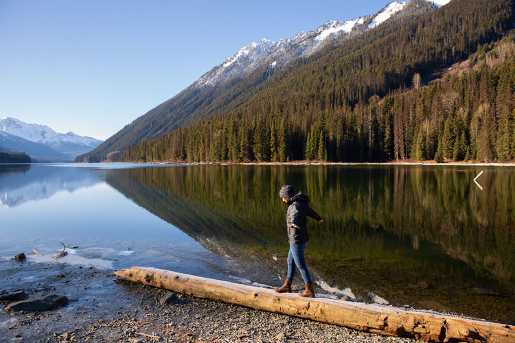 Woman balancing on driftwood at lake with mountains Balancing Standing person Woman Females Log Driftwood Canada British Columbia Pacific Northwest  Mountain Range Mountains Beach Landscape Fall Springtime Water Calm Water Still Water
